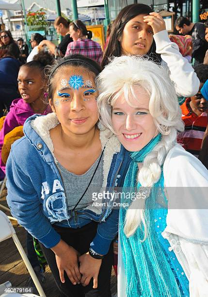 A woman dressed as 'Elsa' from Disney's 'Frozen' paints faces at The Heartfelt Foundation 35th Annual Christmas/Holiday Service Project held at Santa...