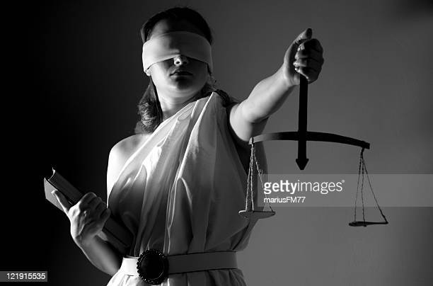 A woman dressed as justice with scales and blindfold