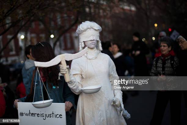 A woman dressed as Lady Justice attends a rally to mark International Women's Day in Washington Square Park March 8 2017 in New York City The rally...