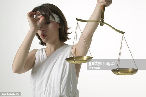 Woman dressed as lady justice peeking at scales