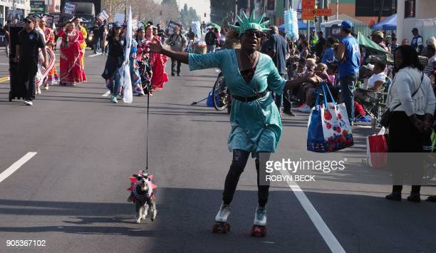 A woman dressed as Lady Liberty to promote Liberty Tax Service roller skates with her dog during the 33rd annual Kingdom Day Parade honoring Dr...