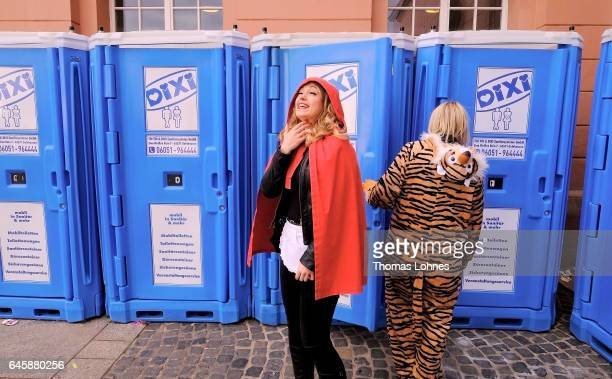 A woman dressed as 'Little Red Riding Hood' pictured in front of toilets during the annual Rose Monday parade on February 27 2017 in Mainz Germany...