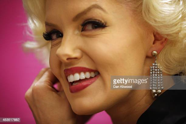 A woman dressed as Marilyn Monroe poses with earrings during a photocall at Christie's Auction House on August 12 2014 in London England The earings...