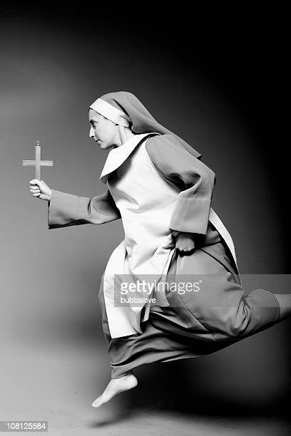 woman dressed as nun, running and holding cross - nun stock pictures, royalty-free photos & images