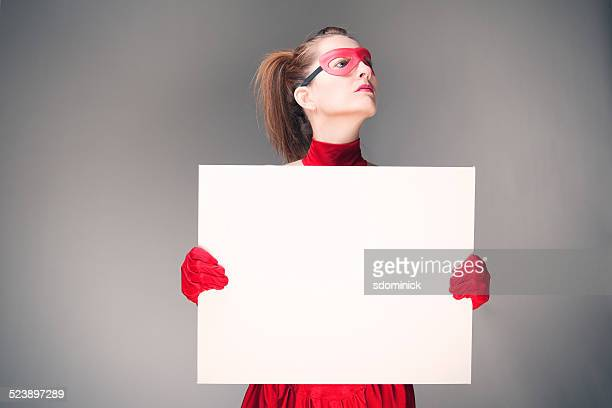 woman dressed as superhero holding blank sign - blank sign stock photos and pictures
