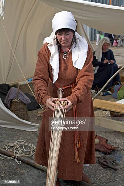 Woman dressed as Viking demonstrating process of rope making