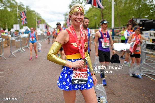 TOPSHOT A woman dressed as Wonder Woman recovers after running the 2019 London Marathon in central London on April 28 2019 / Restricted to editorial...