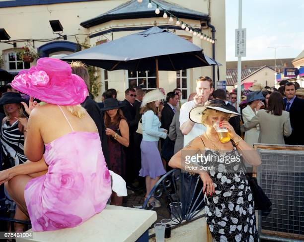 A woman dressed for Ladies Day drinks from a plastic pint glass outside a pub next to Royal Ascot Racecourse June 2001