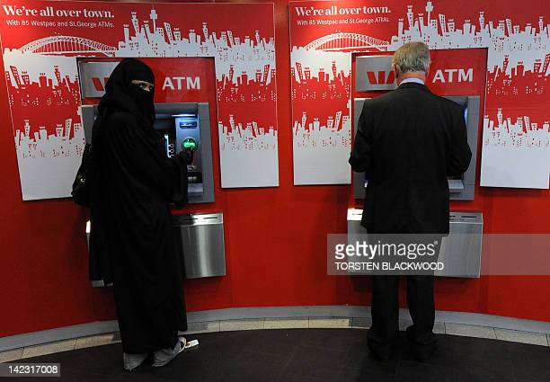 A woman dressed in a burqa from the group 'Faceless' withdraws cash from an ATM during an antiburqa rally in Sydney on April 2 2012 The group says...