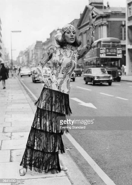 A woman dressed in a fringed skirt hailing a taxi