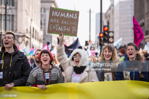 A woman dressed in a furry coat holds up a placard while singing during a protest against climate change in the middle of Oxford Circus on 15th April...