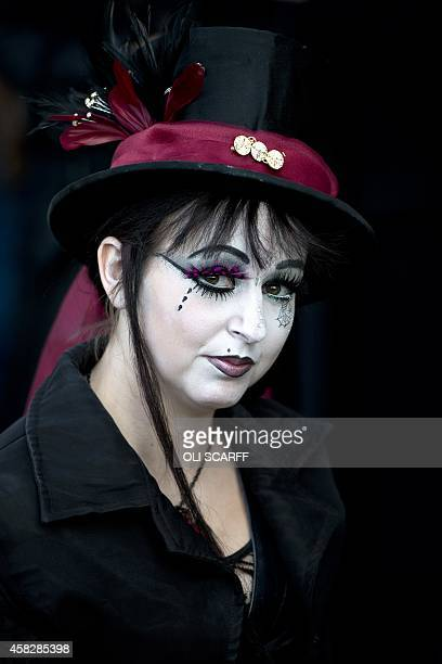 A woman dressed in a gothic costume poses for a picture during the biannual Whitby Goth Weekend festival in Whitby Northern England on November 2...