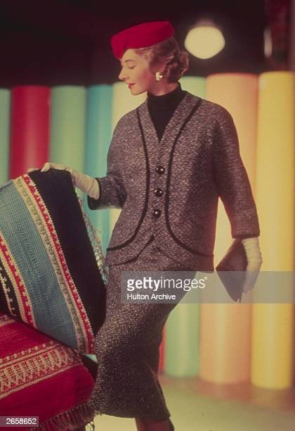 A woman dressed in a grey suit with threequarter sleeves and red pillbox hat looking at a selection of striped rugs