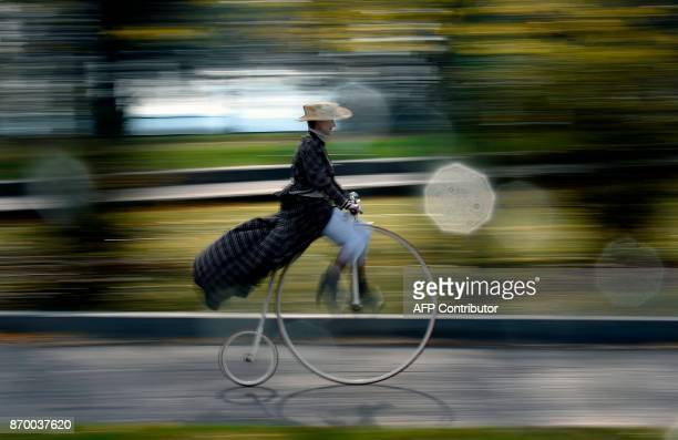 A woman dressed in a historical costume rides her pennyfarthing bicycle also known as high wheel during the traditional 'One Mile Race' competition...
