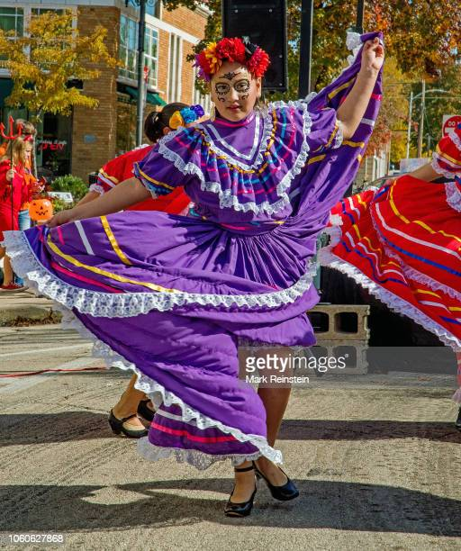 A woman dressed in a traditional La Calavera Catrina costume dances the Jarabe Tapatio during the Day of the Dead event held in downtown Emporia...