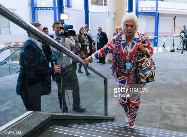 A woman dressed in a Union Flag suit climbs the stairs inside the International Convention Centre on the final day of the Conservative party...