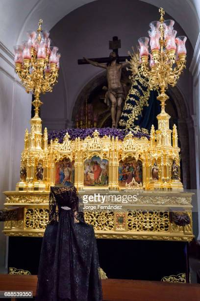 Woman dressed in a very old fashion way with the traditional 'mantilla' and 'peineta' praying inside a church In Seville during what is known as...