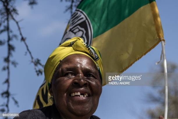 A woman dressed in African National Congress regalia waits outside the Fourways Memorial Park cemetery in Johannesburg on April 14 ahead of the...