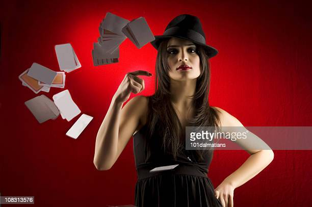 Woman dressed in black dress and hat tosses cards at camera