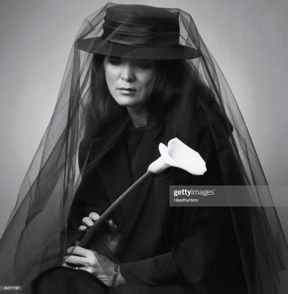 Woman dressed in black, holding flower : Stock Photo