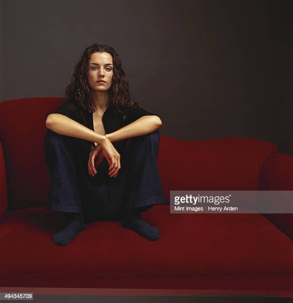 a woman dressed in black seated on a red couch. - only mid adult women stock pictures, royalty-free photos & images