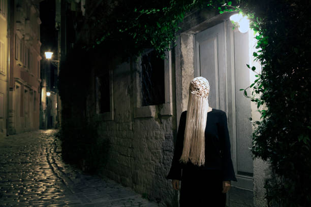 Woman dressed in black wearing crocheted white headdress with fringes at night, Rovinj, Croatia