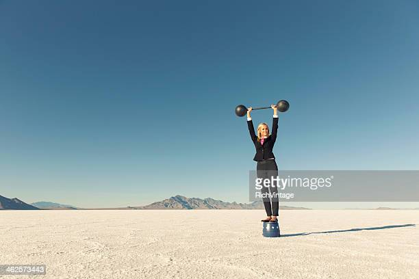 Woman Dressed in Business Suit Lifts Barbell on Salt Flats