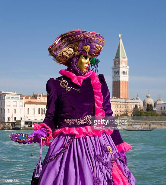 Woman dressed in carnival costume and mask posing in front of the Campanile di San Marco during the Venice Carnival, Punta della Dogana, Dorsoduro district.