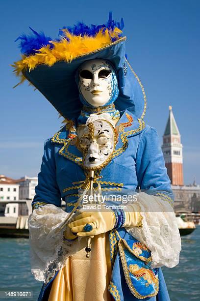 woman dressed in carnival costume and mask posing in front of the campanile di san marco during the venice carnival, punta della dogana, dorsoduro district. - プンタデラドガーナ ストックフォトと画像