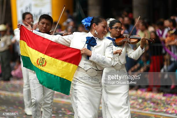 Woman dressed in charro shows the flag of his country, Bolivia, one of the countries that participated with a mariachi band for the XX International...