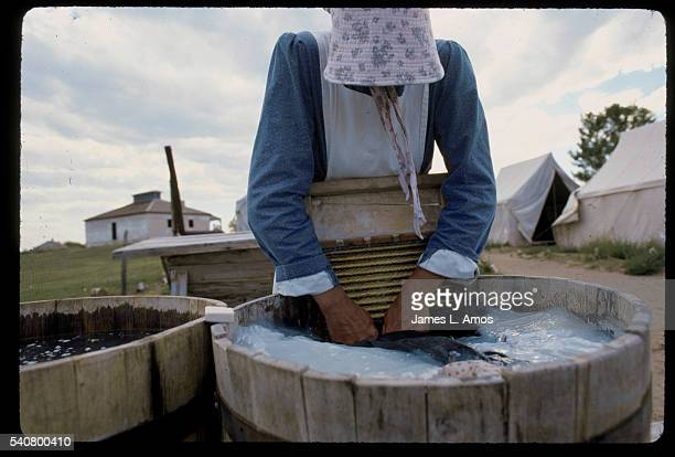 A woman dressed in historic costume washes clothing on a washboard in a barrel as part of an historical reenactment of pioneer life on the Oregon...