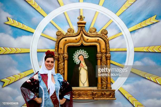 A woman dressed in Madrid's traditional attire Chulapos poses during the Feast of La Paloma Virgin in Madrid on August 13 2018 Madrid's history and...