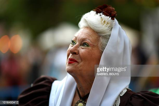 A woman dressed in Madrid's traditional attire Chulapos smiles during the Feast of La Paloma Virgin in Madrid on August 13 2018 Madrid's history and...
