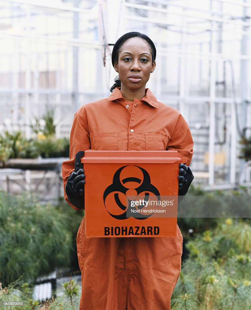 Woman Dressed in Protective Clothing Holding a Hazardous Box in a Greenhouse : Stock Photo