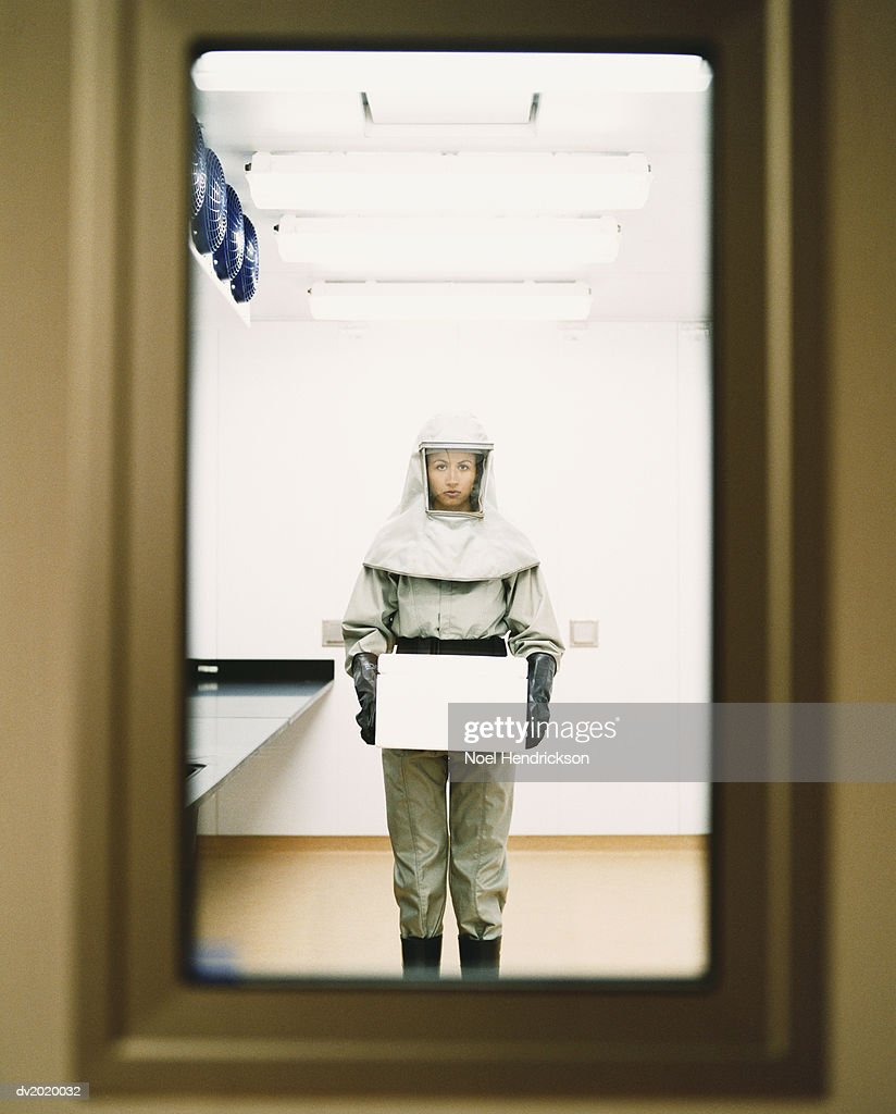 Woman Dressed in Protective Mask and Clothing and Holding a Box : Stock Photo