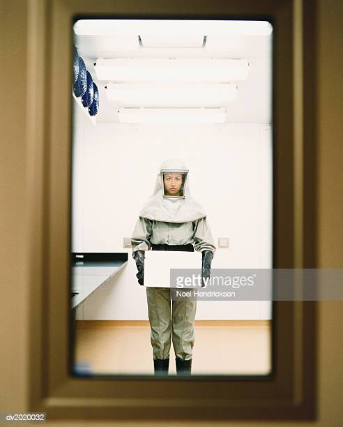 woman dressed in protective mask and clothing and holding a box - hazmat stock pictures, royalty-free photos & images
