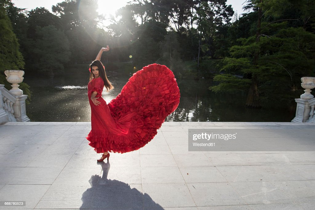 Woman dressed in red dancing flamenco on a terrace in front of a lake : Stock Photo