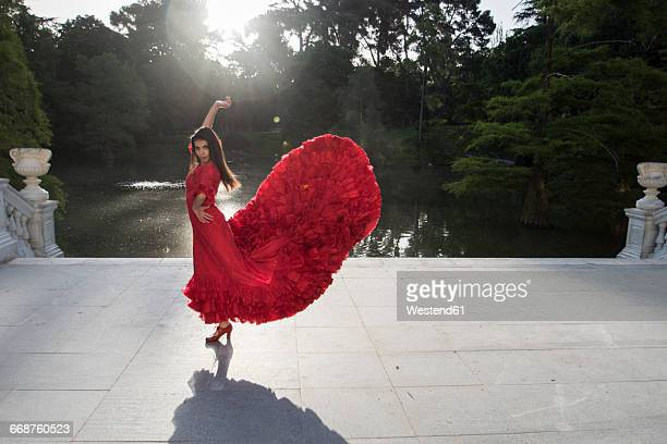 Woman dressed in red dancing flamenco on a terrace in front of a lake