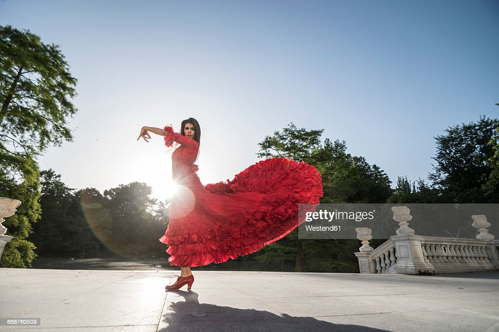 Woman dressed in red dancing flamenco on terrace at backlight : Stock-Foto