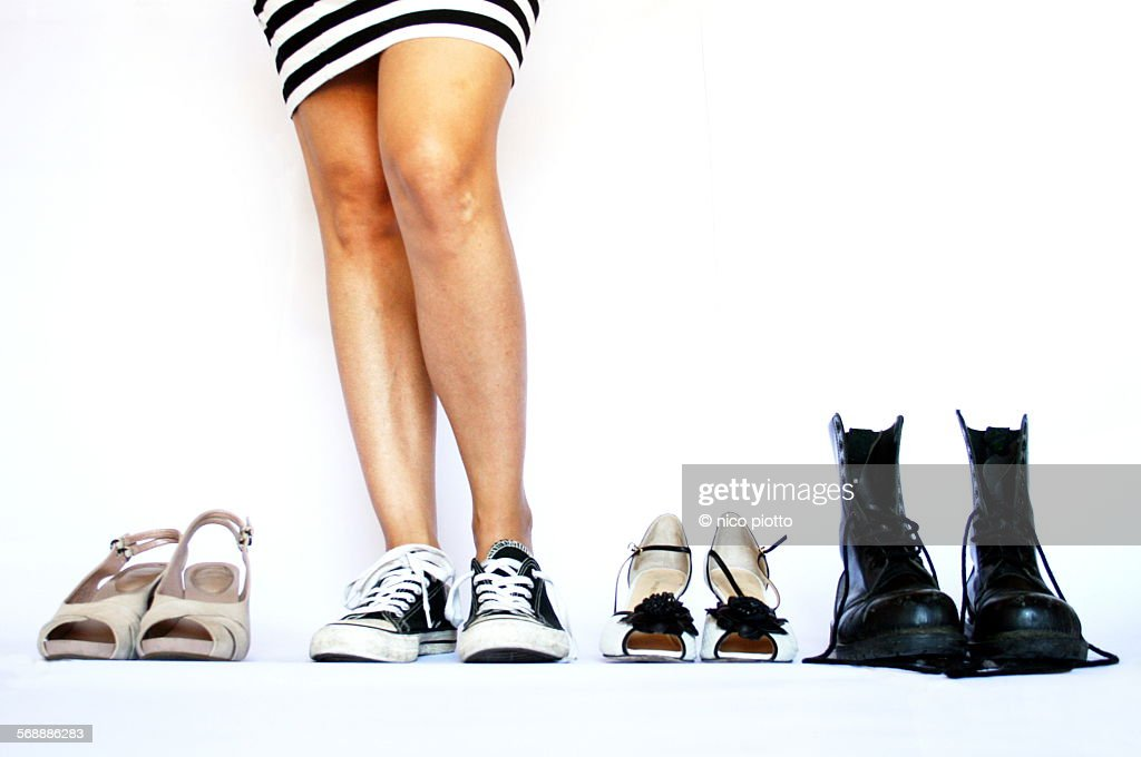 Woman dressed in stripes choosing shoes : Stock Photo
