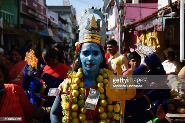 Woman dressed in the style of a Hindu goddess walks along a street during Maha Shivaratri celebrations on March 12, 2021 in Kaveripattinam, India....