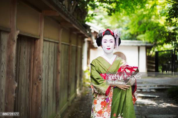 a woman dressed in the traditional geisha style, wearing a kimono and obi, with an elaborate hairstyle and floral hair clips, with white face makeup with bright red lips and dark eyes on a street.  - 優美 ストックフォトと画像