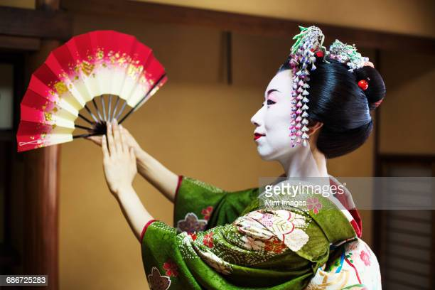 A woman dressed in the traditional geisha style, wearing a kimono and obi, with an elaborate hairstyle and floral hair clips, with white face makeup with bright red lips and dark eyes. Standing in a classic pose with fan raised, side view.