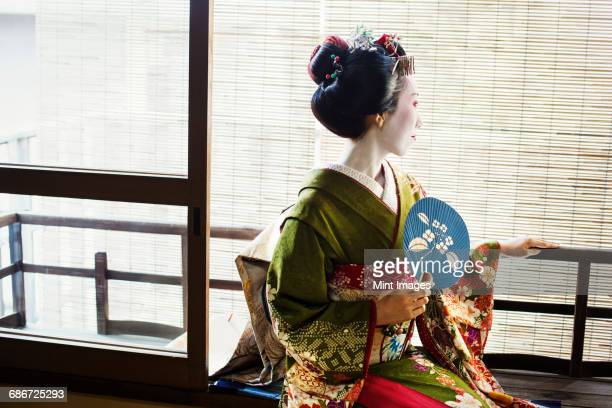 A woman dressed in the traditional geisha style, wearing a kimono and obi, with an elaborate hairstyle and floral hair clips, with white face makeup with bright red lips and dark eyes. Seated by a window with a fan.