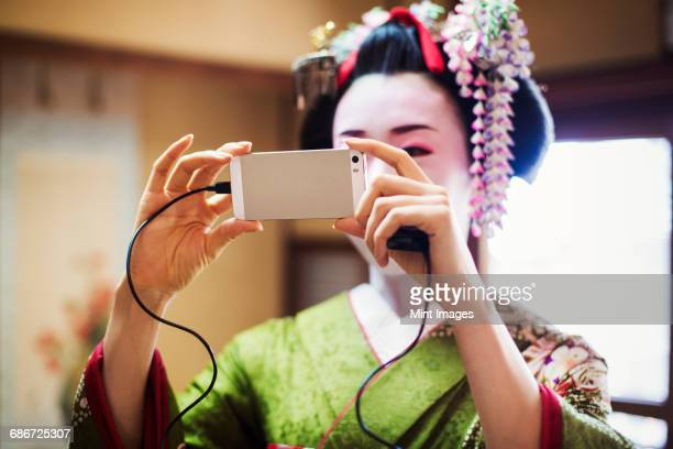 A woman dressed in the traditional geisha style, wearing a kimono and obi, with an elaborate hairstyle and floral hair clips, with white face makeup with bright red lips and dark eyes. Taking a selfie.