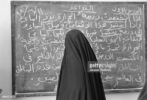 A woman dressed in traditional chador writes on a blackboard at an adult literacy class for women at a vegetable oil factory in the capital Baghdad
