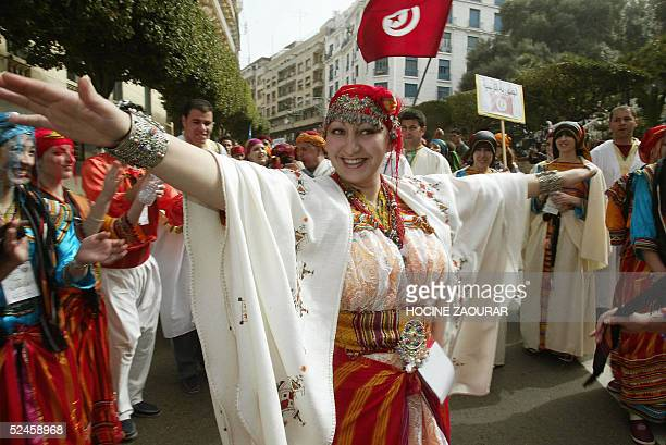 A woman dressed in traditional cloth dances during a parade 20 March 2005 in the streets of Algiers on the eve of the opening of an arab summit in...