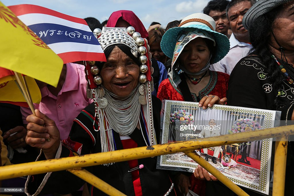 A woman dressed in traditional clothing holds a portrait of Bhumibol Adulyadej, king of Thailand, during the Royal Ploughing Ceremony at Sanam Luang park in Bangkok, Thailand, on Monday, May 9, 2016. This year may be a better one for Thai rice production. At least, that's what two sacred oxen and a ceremonial lord forecast at an annual ploughing ceremony. Photographer: Dario Pignatelli/Bloomberg via Getty Images