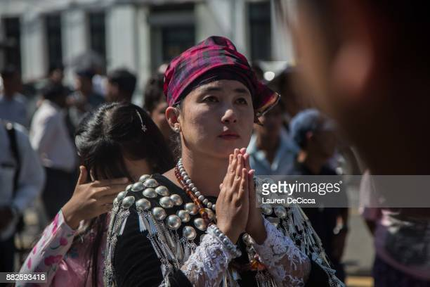 A woman dressed in traditional clothing prays during the Catholic Mass outside St Mary's Catholic Church in downtown during a Mass for Myanmar Youth...
