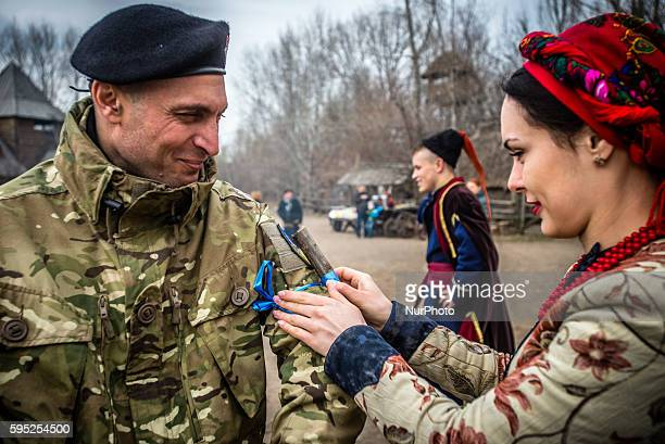 Woman dressed in traditional costume ties a branch on the hand of Georgia National Legion soldier in Mamayeva Sloboda Kyiv Ukraine on March 13 2016